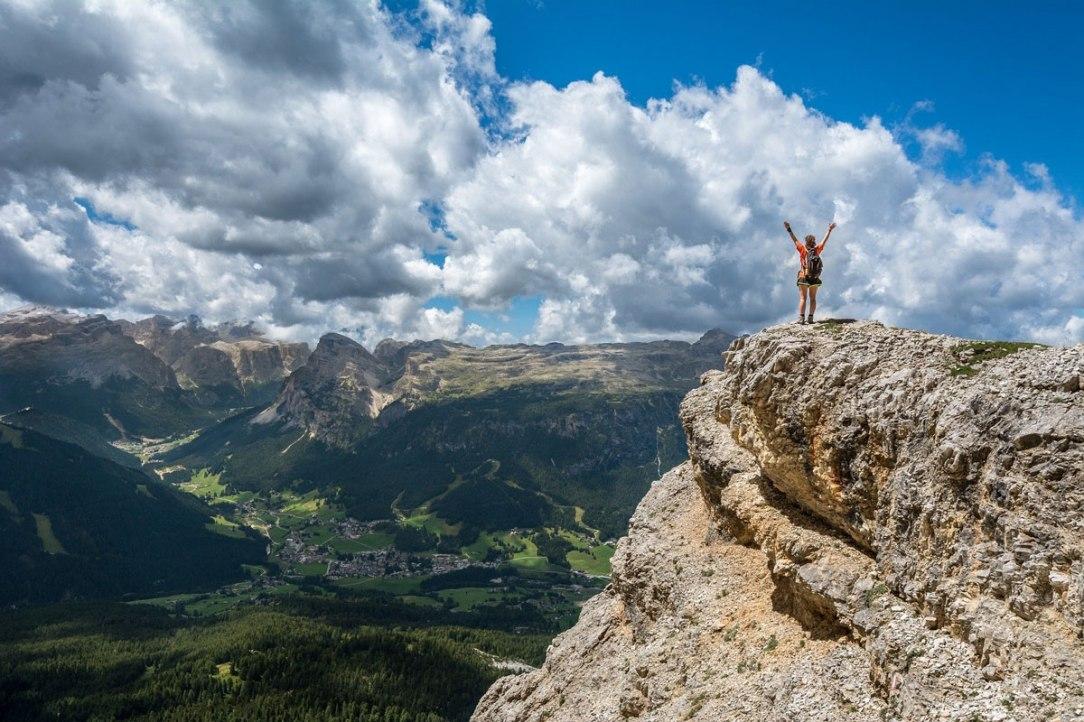 una persona con le braccia alzate in segno di vittoria per aver conquistato una vetta. sullo sfondo una valle verdeggiante