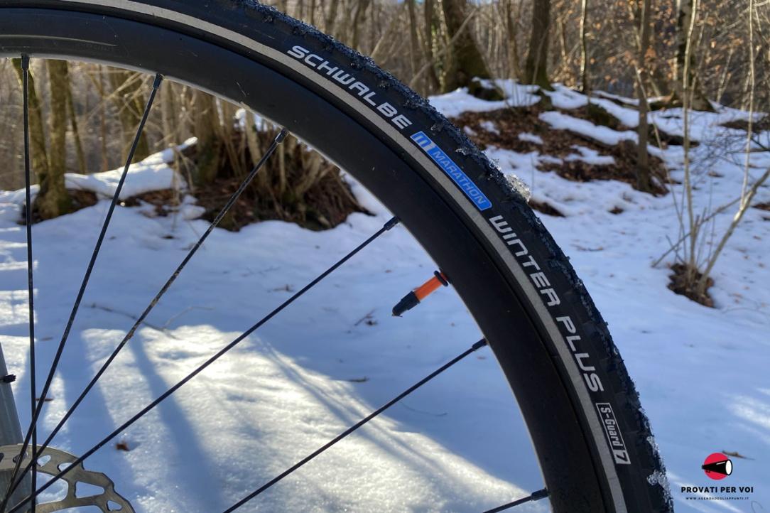 la spalla di uno pneumatico invernale chiodato per bicicletta con scritte e fascia catarifrangente