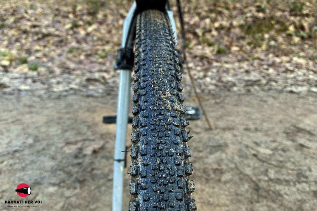 primo piano del battistrada di uno pneumatico per bicicletta gravel bike e sullo sfondo una strada in calcestre e foglie secche