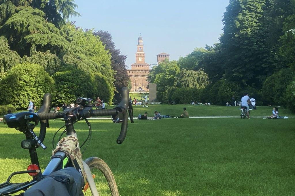 una bicicletta in primo piano, un prato verdeggiante e un castello sullo sfondo
