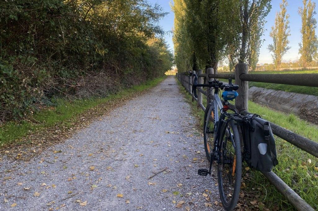 una bicicletta con portapacchi e borsa, una strada di ghiaia