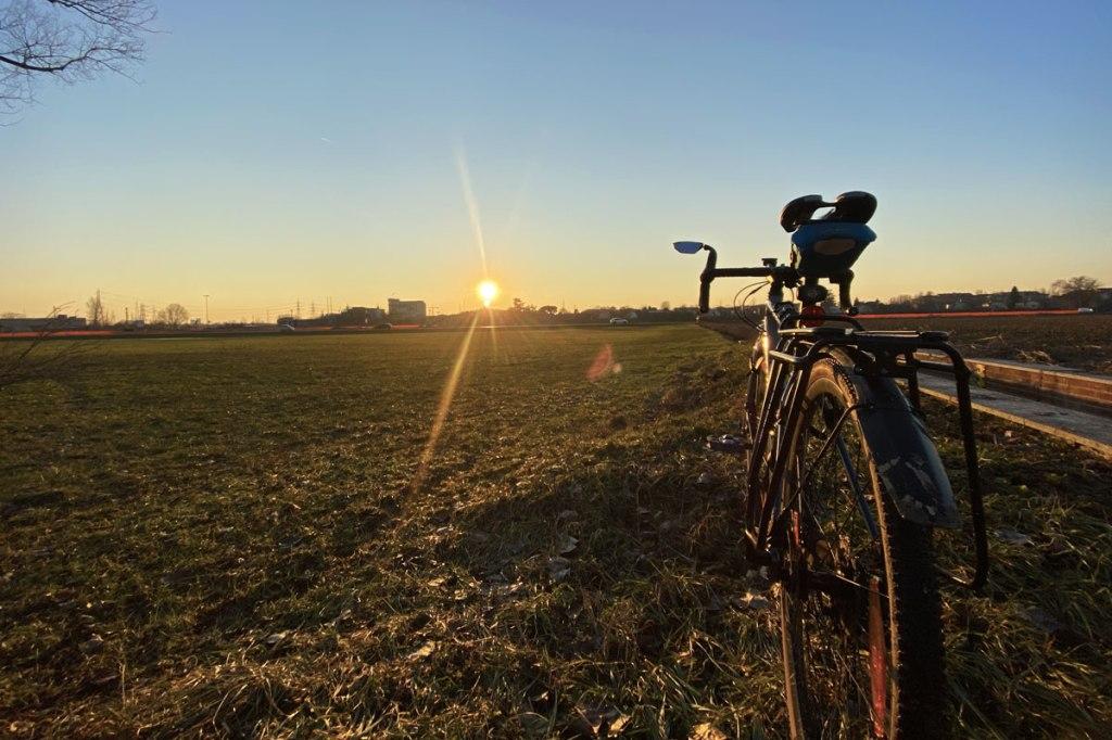 una bicicletta in primo piano fotografata con il sole al tramonto di fronte