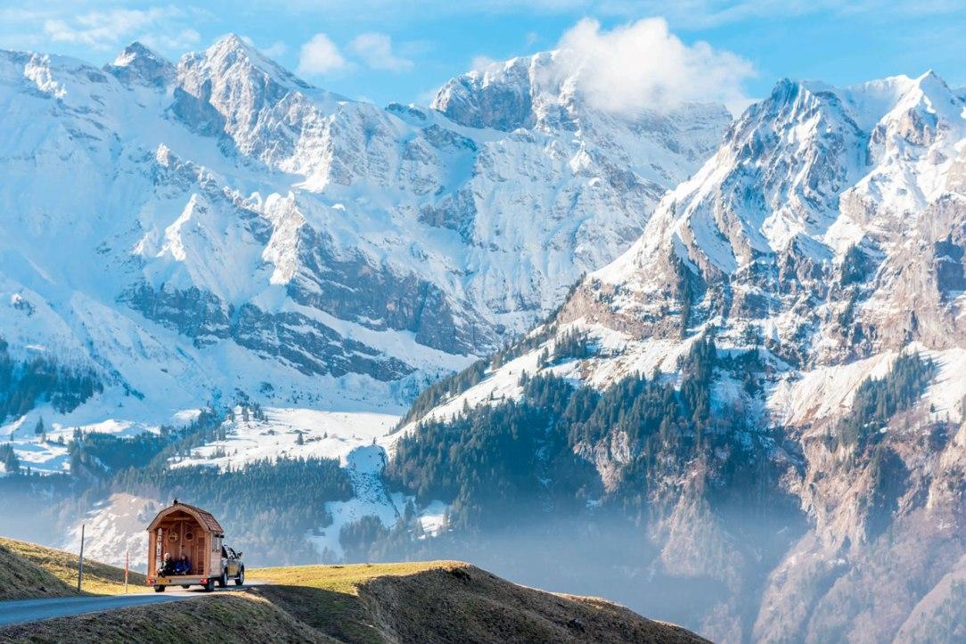 un'autovettura con casa su carrello appendice e sullo sfondo un gruppo di montagne innevate