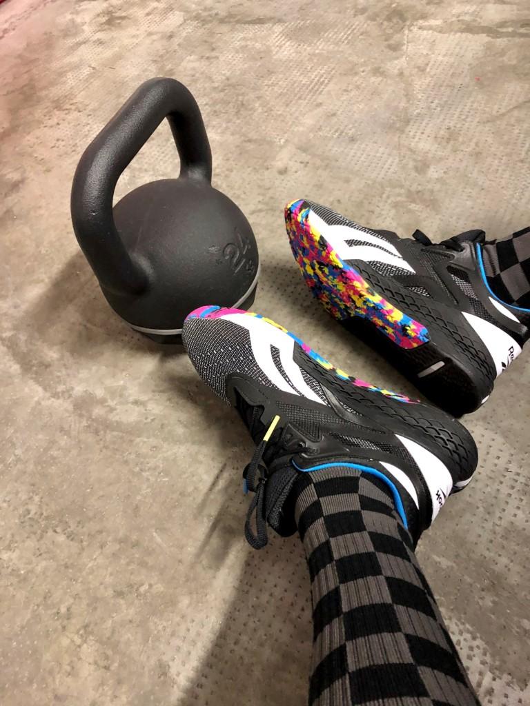 un peso kettlebell da 24 kg ed un paio di scarpe da allenamento crossfit indoor
