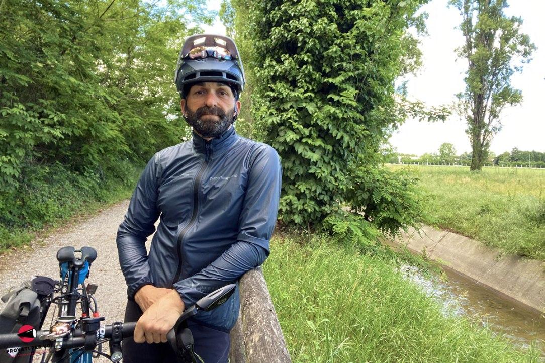 un ragazzo indossa una giacca antipioggia e antivento di fianco alla sua bicicletta all'aperto tra alberi verdi e campi in erba