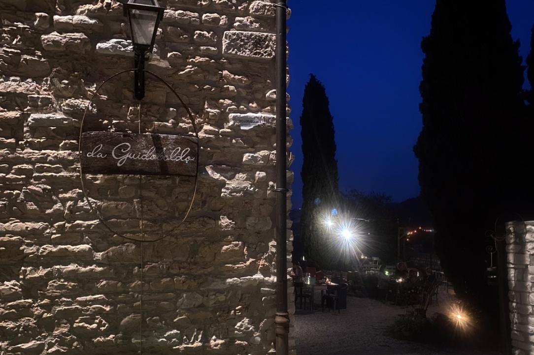 il giardino di un ristorante illuminato di notte ed in primo piano l'insegna su muro di pietra