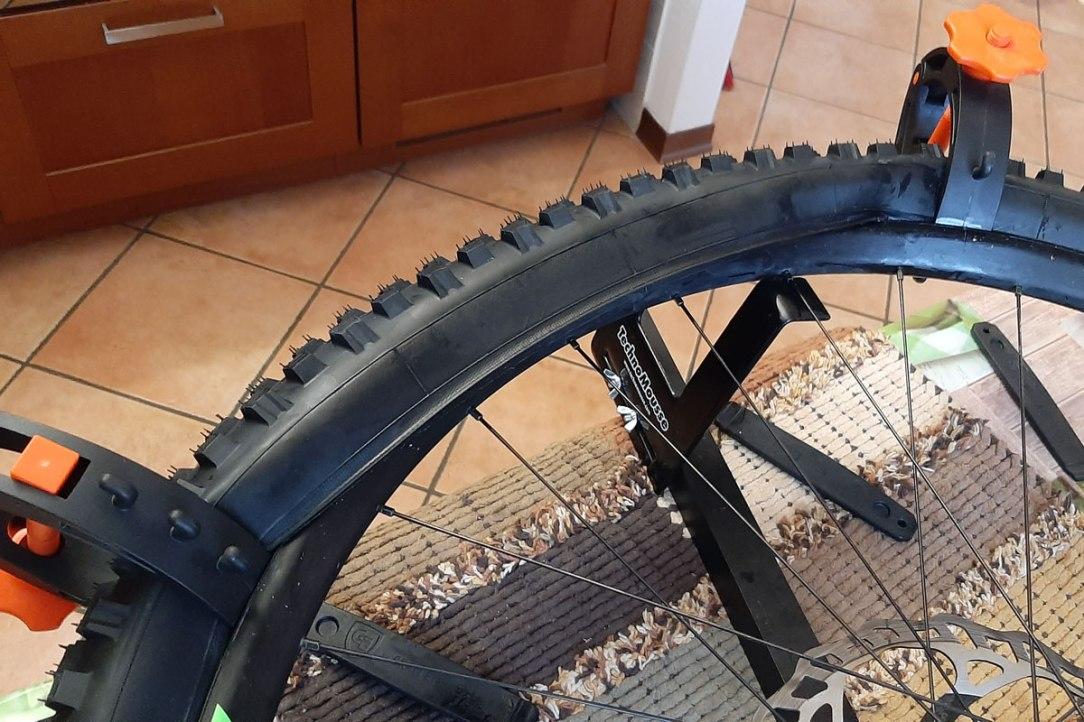 due pinze stringono la spalla dello pneumatico per agevolare il montaggio all'interno del bordo del cerchio