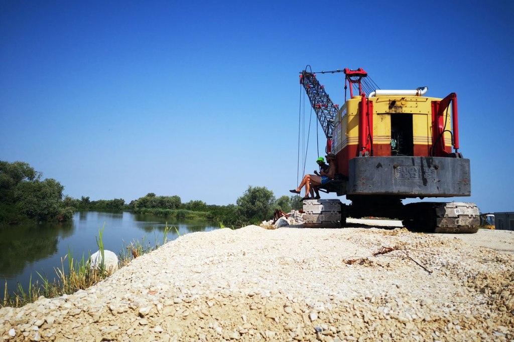 Pausa sugli argini del PO in costruzione con un escavatore in primo piano