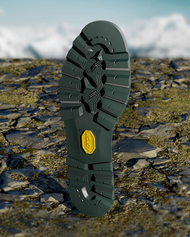 suola per calzature da alpinismo nera con logo Vibram giallo e sfondo di un paesaggio impervio di montagna