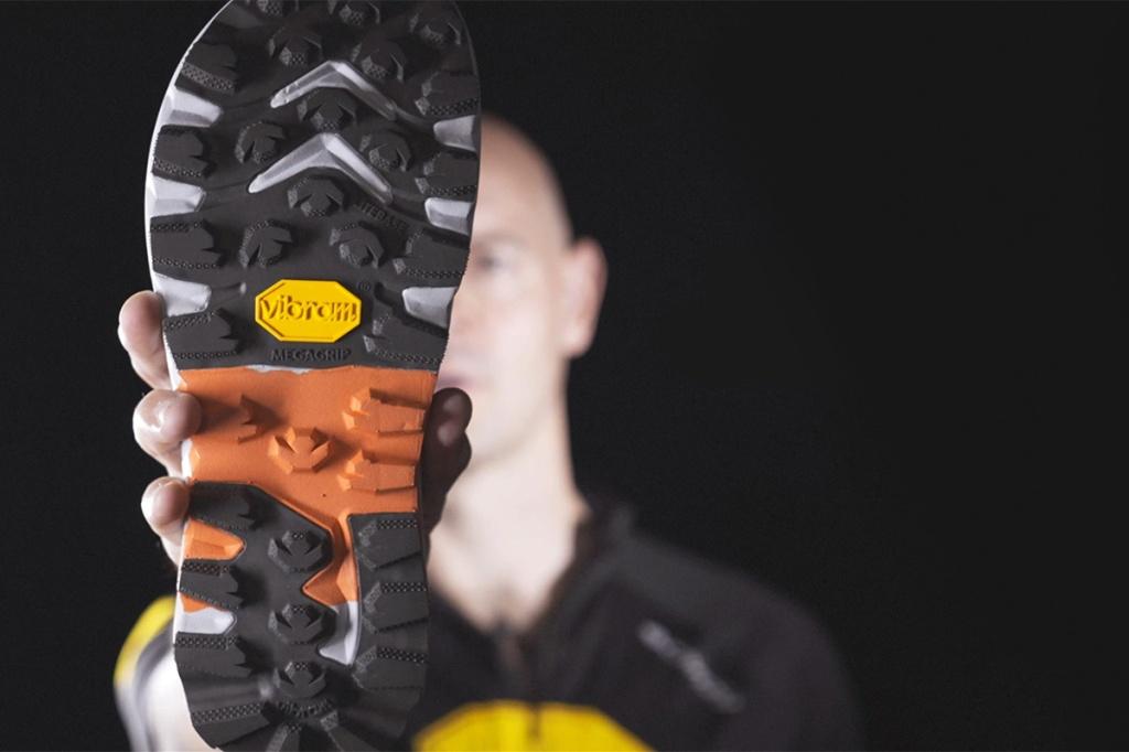 un atleta professionista tiene in mano una suola per calzature da trail running di colore nero e rossa con inserti grigi e logo Vibram giallo
