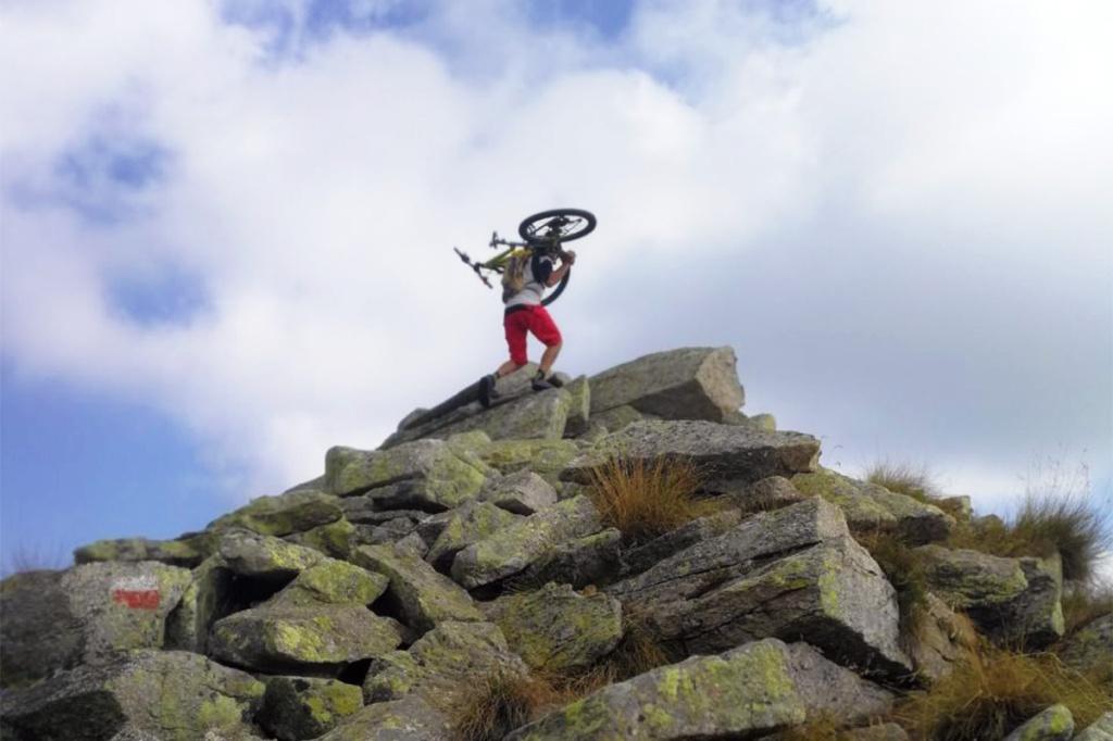 Ragazzo con biciletta in cima alla montagna