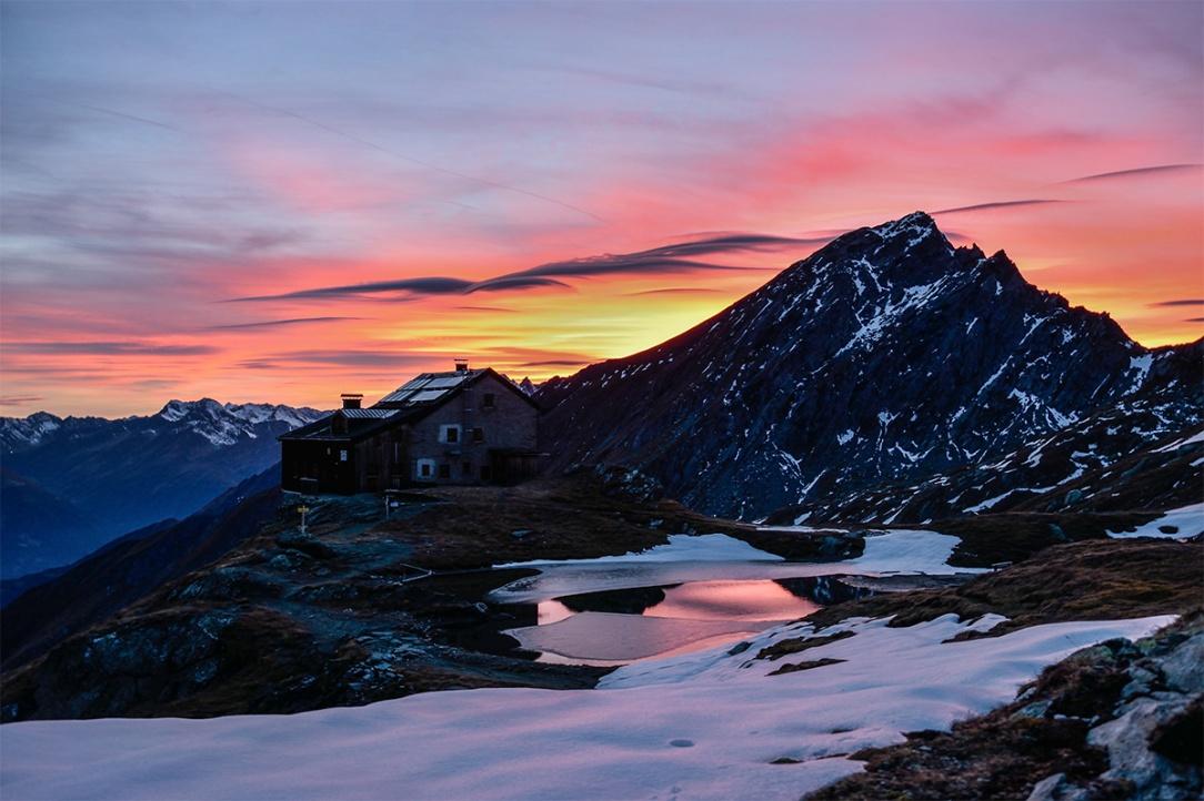 Un rifugio di montagna sulle Alpi vicino ad un laghetto parzialmente coperto dalla neve