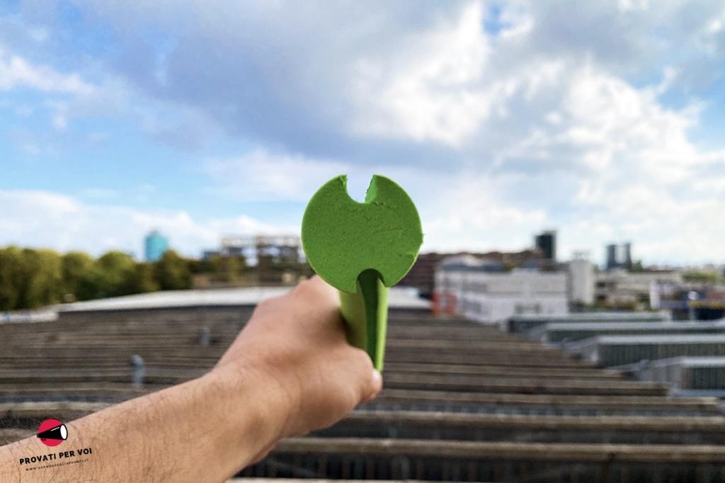 un cilindro in plastica EVA di colore verde visto dalla sezione trasversale e sullo sfondo la skyline milanese